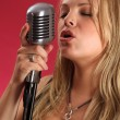 Blond singing into retro microphone - Stock Photo