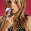 Singing into vintage microphone - Stock Photo