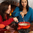 Women dipping bread into fondue — Stock Photo
