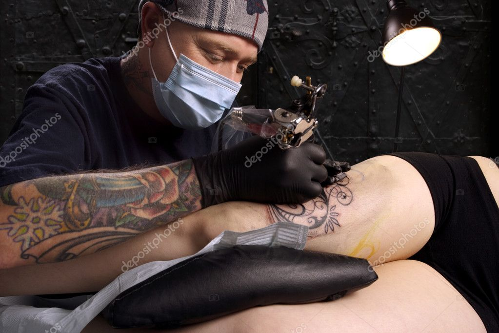 A tattoo artist applying his craft onto the leg of a female. Property release supplied includes tattooists' tattoo and artwork.  Stock Photo #6572127