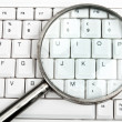 Magnifying glass on keyboard — Stock Photo
