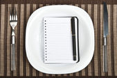 Notepad on food plate — Stockfoto