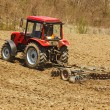 Tractor with disk harrow and rake - Stock Photo