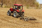 Tractor with disk harrow and rake — Stock Photo