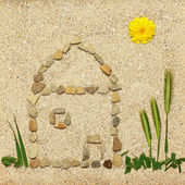 Stone house illustration in sand — Stock Photo