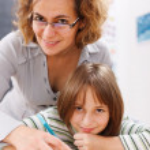 Teacher helping schoolgirl writing — Stock Photo