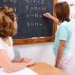 School girl writing solution on chalkboard — Stok fotoğraf