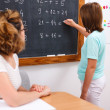 Stock Photo: School girl writing solution on chalkboard