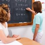 School girl writing solution on chalkboard — Stock Photo