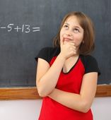 Elementary schoolgirl thinking on solution — Stock Photo