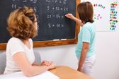 School girl writing solution on chalkboard — Stock Photo