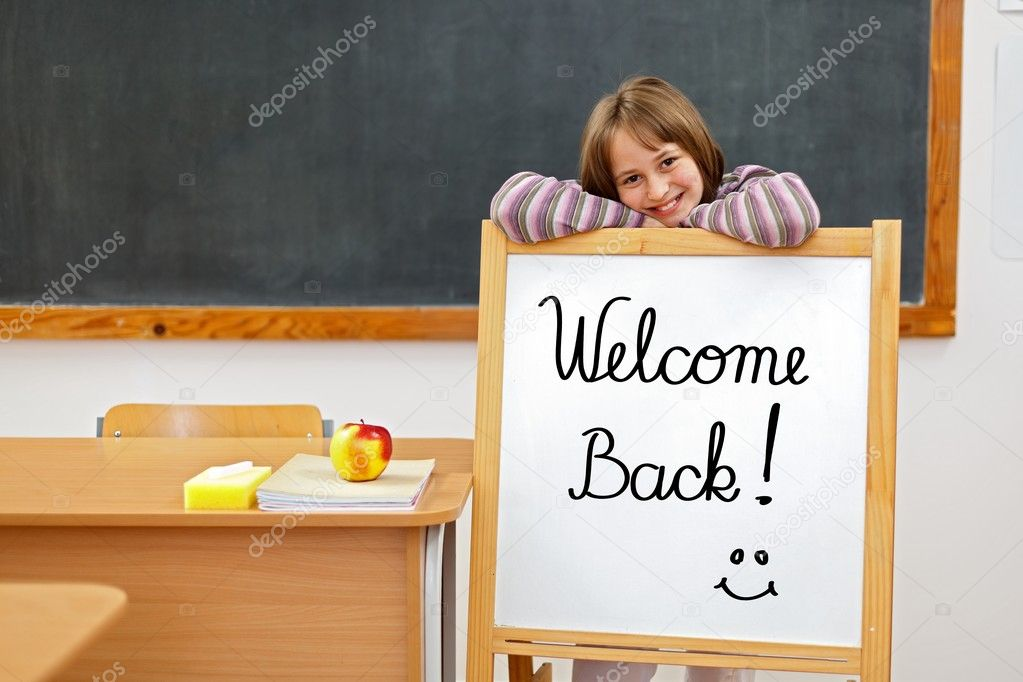School girl in classroom, behind a board with Welcome Back script  Stock Photo #6076016