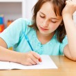 Schoolgirl writing boring homework — Stock Photo