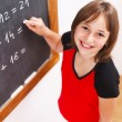 Schoolgirl looking up in front of chalkboard — Stock Photo