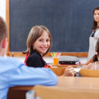 Cheerful schoolgirl in class room — Stock Photo #6161757