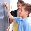Boy writing on chalkboard in front of teacher — Stock Photo