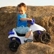 Boy driving toy quad on terrain — Stock Photo
