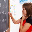 Girl standing in front of chalkboard and thinking — Stock Photo