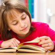 Schoolgirl reading in classroom - Stock Photo