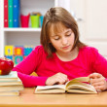 Schoolgirl reading book — Stock Photo