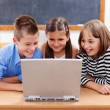 Happy kids looking at laptop — Stockfoto