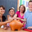 Students and teacher putting coin into piggy bank — Zdjęcie stockowe #6161865