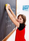 Elementary school student erasing chalkboard — Stock Photo