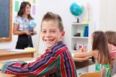 Cheerful young boy in school — Stock Photo