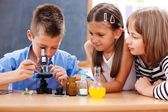 Boy looking into microscope — Stockfoto
