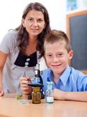 Wise boy with microscope and teacher — Stock Photo