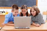 Happy kids looking at laptop — Stock Photo