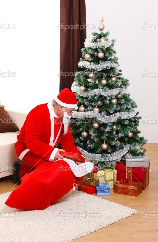 Senior man in Santa Claus uniform, putting presents under Christmas tree from bag — Stock Photo #6161800