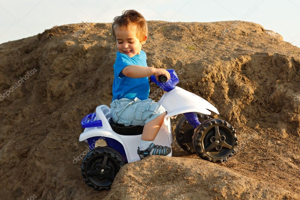 Little boy driving toy quad on terrain — Stock Photo #6161811