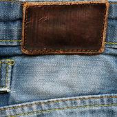 Blank grungy leather label on vintage light blue denim — Stock Photo