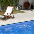 Deckchair in a swimming pool — Stock Photo