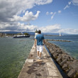 Young man walking in the Jet d'Eau dock in Geneva — Stock Photo