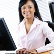 Happy black businesswoman at desk — Stockfoto