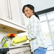 Happy young woman washing dishes — Stock Photo