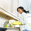 Stock Photo: Young womwashing dishes