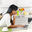 Woman using computer in kitchen - Stock Photo
