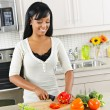 Young woman cutting vegetables in kitchen — Stok fotoğraf #6650881