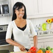 Young woman cutting vegetables in kitchen — Stock Photo #6650893