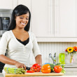 Foto Stock: Young womcutting vegetables in kitchen