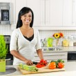 Foto Stock: Young woman cutting vegetables in kitchen