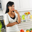 Young woman tasting vegetables in kitchen — Stockfoto