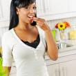 Young woman tasting vegetables in kitchen — Stok fotoğraf #6650933