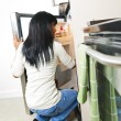 Young woman looking in refrigerator - Stock Photo