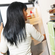 Young woman looking in refrigerator — Stock Photo