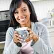Woman in kitchen with coffee cup — Stock Photo