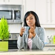 Woman in kitchen with coffee cup - Stock Photo